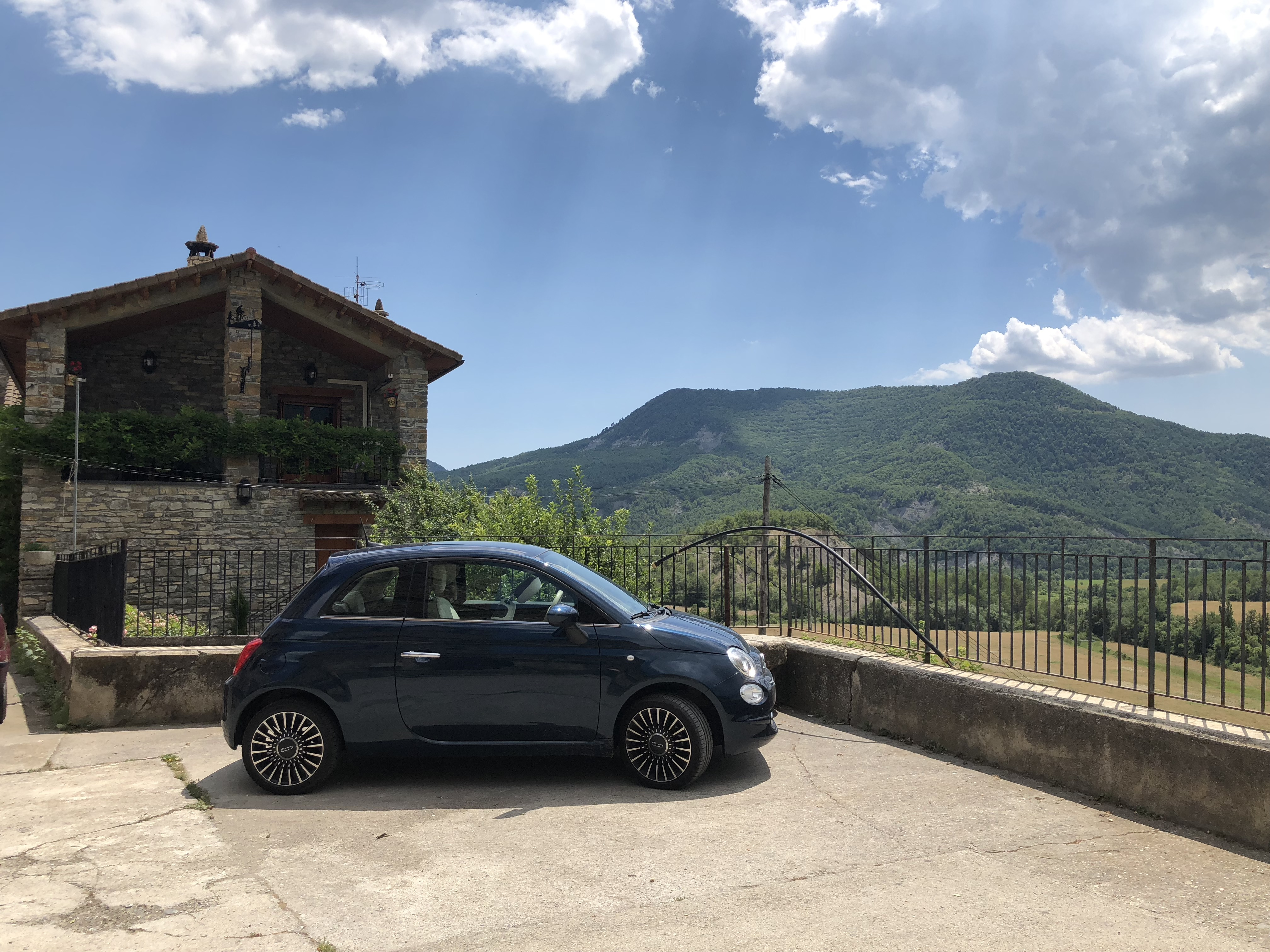 Small blue car in front of building with mountains